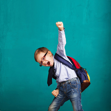 Cheerful smiling little boy with big backpack jumping and having fun against blue wall. Looking at camera. School concept. Back to School Standard-Bild