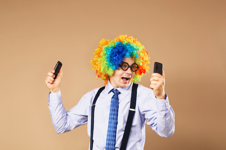 droll: Businessman respond to numerous phone calls. Businessman holding two mobile phones. Close-up Portrait of business man in clown wig. Business concept. Multitasking