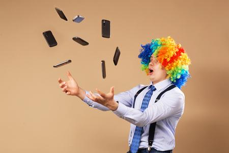 Homme d'affaires attraper les téléphones mobiles tombant d'en haut. Close-up portrait d'homme d'affaires en perruque de clown. Concept d'entreprise
