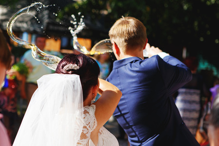 traditions: wedding traditions. Bride and groom pouring out champagne over the left shoulder Stock Photo