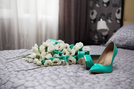 attributes: Bride attributes. Morning of the bride. Wedding bouquet of white roses and blue ribbons and blue patent leather high-heeled shoes. Preparations for the wedding ceremony Stock Photo