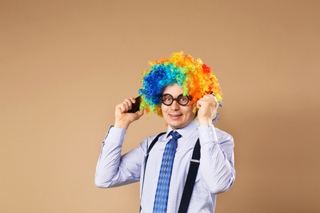 respond: Businessman respond to numerous phone calls. Businessman holding two mobile phones. Close-up Portrait of business man in clown wig. Business concept