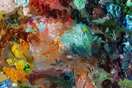 saturation: artists oil paints on wooden palette. macro artists palette, texture mixed oil paints in different colors and saturation. art palette background Stock Photo
