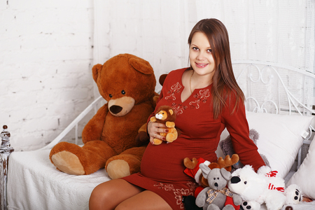 soft toys: Beautiful pregnant woman with soft toys