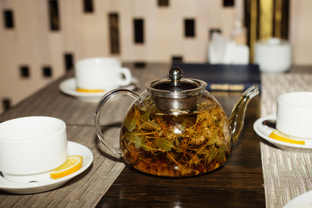 teas: Glass teapot and cups with herbal tea on wooden table. Teapot and cups with linden tea. herbal tea with aroma fresh herb Stock Photo