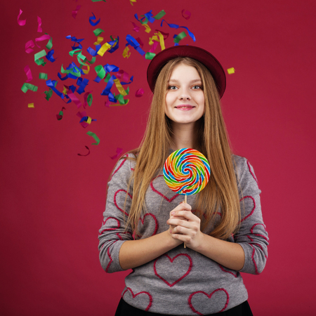 trumpery: Portrait of a teen girl throws up a multi-colored tinsel and confetti. beautiful girl wearing hat holding big striped lollipop Stock Photo