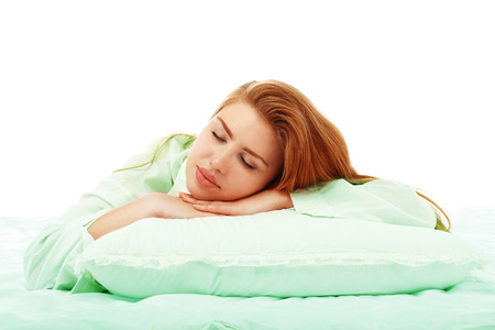 Young beautiful girl sleeps in the bed hugging a pillow on his stomach. Healthy sleep. Isolated on white background. Foto de archivo