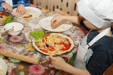 Kinderen maken pizza. Masterclass voor kinderen op koken Italiaanse pizza. Jonge kinderen leren om een pizza te koken. Kinderen de voorbereiding van zelfgemaakte pizza. Little kok. Stockfoto
