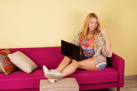 pay wall: Pretty young woman using her laptop while relaxing on a sofa at home. Girl in living room. Beautiful cheerful woman with happy smile sitting on the sofa with laptop Stock Photo
