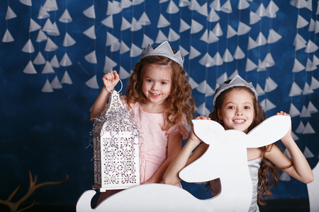 corona navidad: Little girls in christmas decorations. Portrait of Beautiful little girls with long curly hair with crown. Decor winter forest. Little Princess Foto de archivo