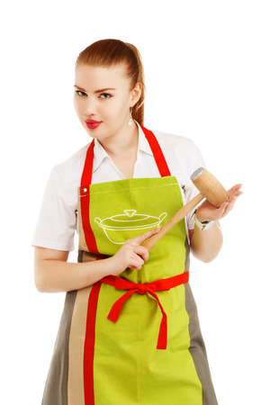 sexy housewife: Portrait of angry housewife with a meat hammer in her hands. Sexy housewife or baker chef wearing kitchen apron holds meat hammer isolated on white background