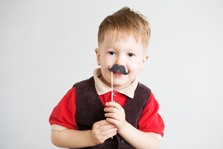 Portrait of a cute little boy with funny photo props paper mustache against a white background