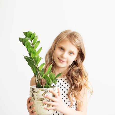 houseplant: Portrait of a lovely little girl with green houseplant against a white background