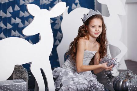 corona navidad: Ni�a en decoraciones de Navidad. Retrato de la ni�a hermosa con el pelo largo y rizado con la corona. bosque de invierno decoraci�n. Peque�a princesa