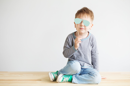 blind child: Portrait of a adorable little kid with blue paper glasses against a white background. A blind child Stock Photo