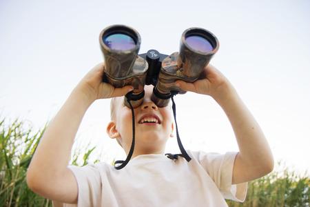 看通过双筒望远镜的小男孩画象在河岸。可爱的孩子与双筒望远镜。这个男孩通过双筒望远镜抬头看着天空