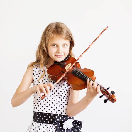 gifted: Portrait of the little violinist. Beautiful gifted little girl playing on violin against the white background
