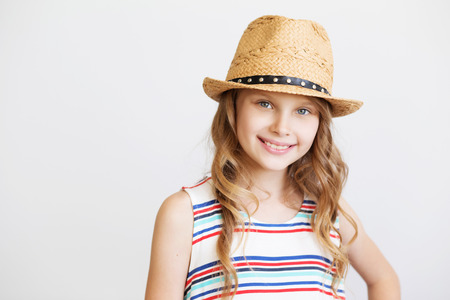 lovely little girl with straw hat against a white background. Smiling kids Foto de archivo