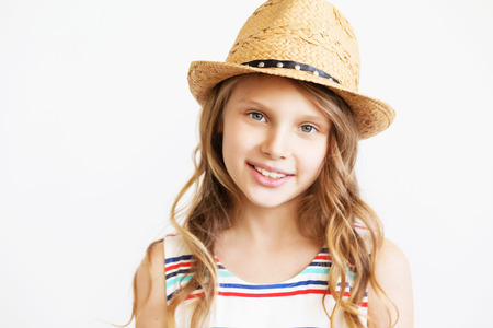 Closeup portrait of a lovely little girl with straw hat against a white background