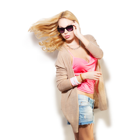 denim shorts: Fashion model girl portrait dressed in pink top, cardigan, denim shorts, sunglasses and modern accessories. Street fashion, casual style. Isolated on white background