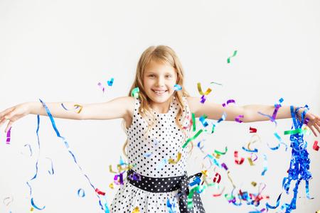 trumpery: Little girl jumping and having fun celebrating birthday. Portrait of a child throws up multi-colored tinsel and confetti. Positive emotions. Happy excited laughing kid under sparkling confetti shower