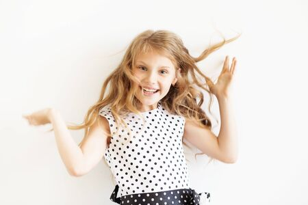 frisky: Lovely frisky little girl in a polka-dot dress jumping and having fun against a white background. Happy kids