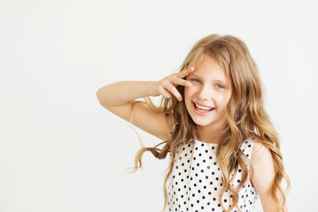 frisky: Lovely frisky little girl in a polka-dot dress against a white background. Happy kids