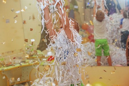 Little boy jumping and having fun celebrating birthday. Portrait of a child throws up multi-colored tinsel and paper confetti. Kids party. Happy excited laughing kid under sparkling confetti shower