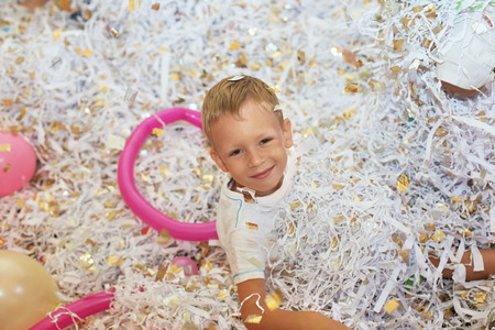frippery: Little boy jumping and having fun celebrating birthday. Portrait of a child throws up multi-colored tinsel and paper confetti. Kids party. Happy excited laughing kid under sparkling confetti shower