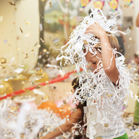 trumpery: Little boy jumping and having fun celebrating birthday. Portrait of a child throws up multi-colored tinsel and paper confetti. Kids party. Happy excited laughing kid under sparkling confetti shower