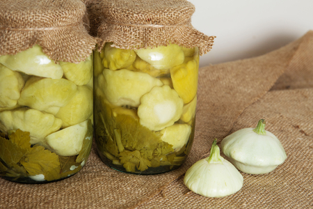 Transparent banks with marinated baby summer squash. Home canning. Banks pickled squash
