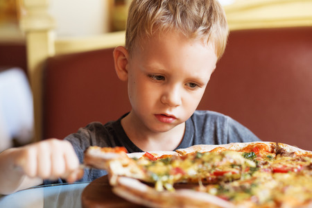 Children eat Italian pizza in the cafe. Adorable little boy eating pizza at a restaurant 写真素材