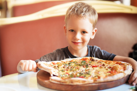 Children eat Italian pizza in the cafe. Adorable little boy eating pizza at a restaurant Stock fotó