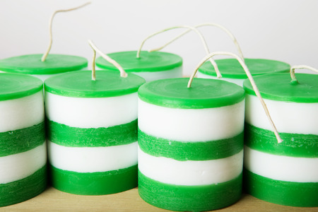 metier: White and green striped cylindrical handmade candles on wood background