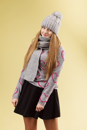 Cute teenage girl wearing gray woolen cap and scarf against yellow background