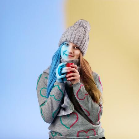 gefesselt: Cute Teenager-Mädchen tragen graue Wollmütze und Schal wärmt sich die Hände an einer Tasse heißen Tee. Gefrorenes Mädchen auftaut heißen Tee