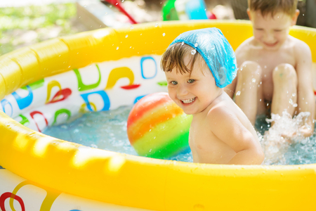 Little children bathe in yellow Inflatable Swimming Paddling Pool outdoors in hot summer day. Kids splashing water and having fun in Swim Pool