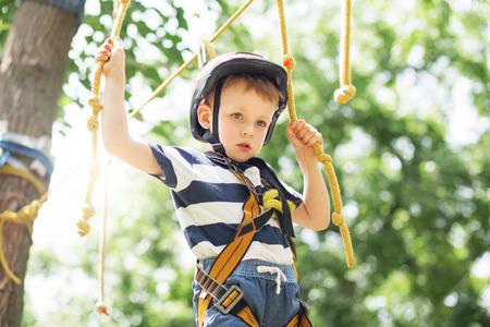 Los niños de escalada en el parque de aventuras. Niño disfruta de la escalada en la aventura circuito de cuerdas. Niño que sube parque cuerda floja. Felices los niños jugando en el parque de aventura, que sostienen las cuerdas y subir escaleras de madera.