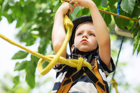 Girl climbing in adventure park is a place which can contain a wide variety of elements, such as rope climbing exercises, obstacle courses and zip-lines. boy enjoys climbing in the ropes course adventure. smiling child engaged climbing high wire park. Hap