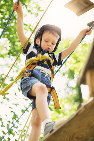 Kids climbing in adventure park. Boy enjoys climbing in the ropes course adventure. Child climbing high wire park. Happy boys playing at adventure park, holding ropes and climbing wooden stairs.