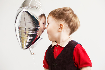 Boy grimacing and playing the ape with star-shaped balloons in studio. Kid looks and rejoices at his reflection in foil balloon. Child laughing looking at the reflection in a distorted mirror