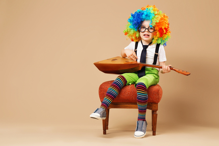 laughable: Blithesome children. Happy clown boy in large neon colored wig playing the balalaika and singing. Portrait of kid wearing clown wig and eyeglasses