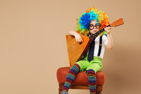 Blithesome children. Happy clown boy in large neon colored wig playing the balalaika. Portrait of kid wearing clown wig and eyeglasses