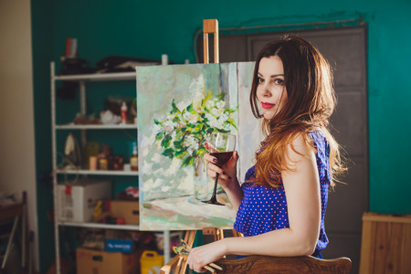 Woman artist painting a picture in a studio. Creative pensive painter girl paints a colorful picture on canvas with oil colors in workshop. Foto de archivo