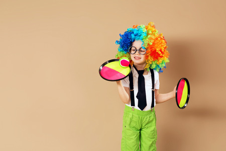 Blithesome children. Portrait of happy clown boy wearing large neon coloured wig. Kid in clown wig and eyeglasses playing catch ball game Stock Photo