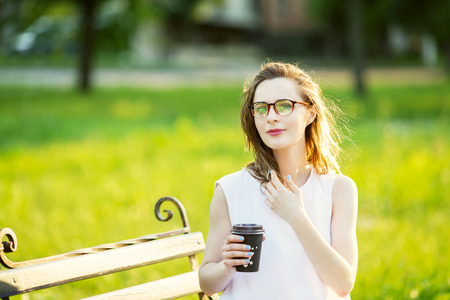 wearing spectacles: Portrait of lovely urban girl with paper cup in her hands. Happy smiling woman walking in a city park. Fashionable blonde girl wearing spectacles