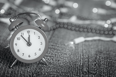 Christmas composition - red alarm clock on a textured wooden board with lights and beads bokeh Stock Photo