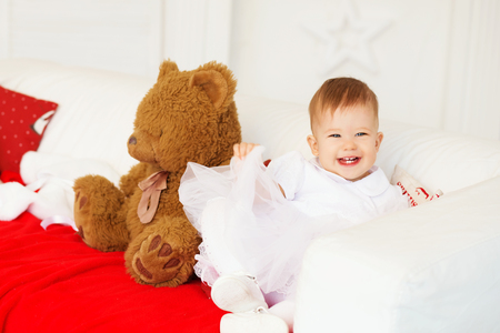 beautiful baby girl laughing and having fun sitting on the couch in the interior with Christmas decorations.