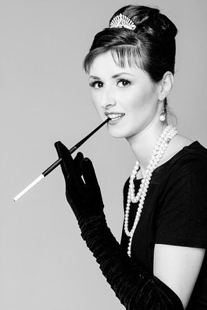 velvet dress: Portrait of a beautiful young woman in retro style with cigarette in mouthpiece in the image of the famous actress Audrey Hepburn. Black and white photography