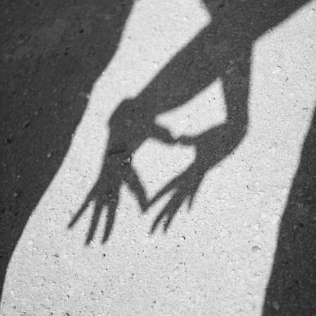 inseparable: Two hands forming a heart shadow on the asphalt. Black and white photography